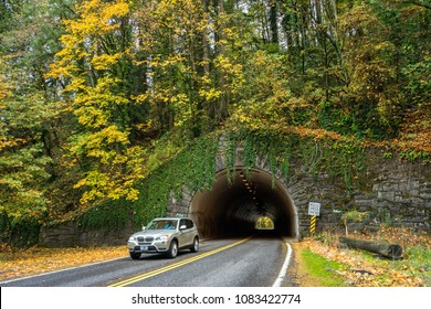 PORTLAND, OREGON - CIRCA NOVEMBER 2017: Vehicles drive through a stone tunnel leading to the entrance of Forest Park, the largest park in Portland, Oregon.