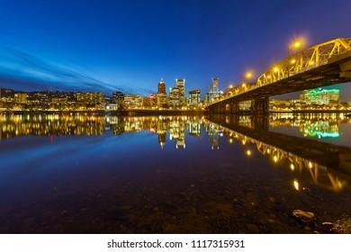 Portland Oregon city downtown skyline by Hawthorne Bridge during evening blue hour