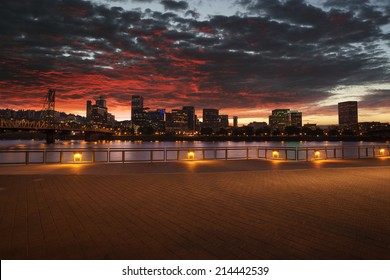 Portland, Oregon city skyline panorama with Hawthorne bridge. Cloudy sunset with dramatic sky and light reflection on the Willamette river.