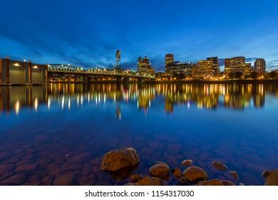 Portland Oregon downtown city skyline by Hawthorne Bridge from Eastbank Esplanade during evening blue hour