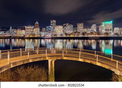 Portland Oregon downtown city skyline from pedestrian bridge along Willamette River at night