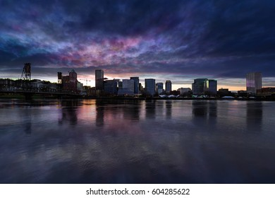Portland Oregon downtown city skyline from Eastbank Esplanade along Willamette River waterfront during cloudy twilight evening