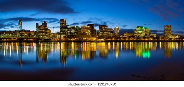 Portland Oregon downtown city skylinw by Hawthorne Bridge along Willamette River at evening blue hour panorama