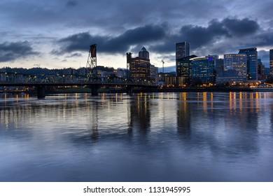 Portland Oregon downtown city skylinw by Hawthorne Bridge along Willamette River at evening blue hour