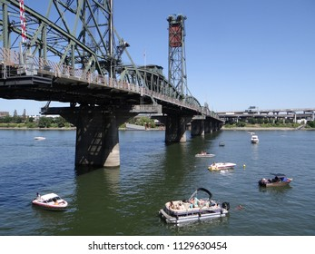 PORTLAND, OREGON - JUL 5, 2018 - Pleasure boats on the Willamette River float under the Hawthorne Bridge in  Portland, Oregon