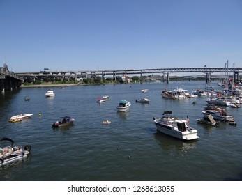 PORTLAND, OREGON - JUL 5, 2018 - Pleasure boats on the Willamette River float under the Hawthorne Bridge in Waterfront Blues Festival, Portland, Oregon