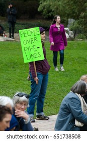 """PORTLAND, OREGON MARCH 10 2017, Protester of the Dakota Access Pipeline (DAPL) holding a sign reading """"People over pipelines""""  in the downtown Terry Shrunk Plaza park."""