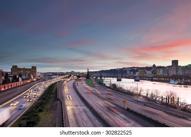 Portland Oregon rush hour traffic with city skyline along Interstate freeway during sunset evening