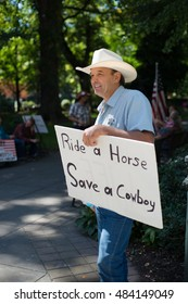 PORTLAND, OREGON SEPTEMBER 14 2016, Protester of the trial of the armed occupation of the Malheur National Wildlife Refuge wearing a cowboy hat and fake Sheriff badge as he holds a sign.