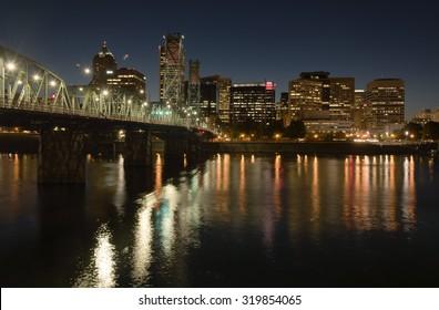 Portland Oregon skyline buildings and bridge at night.