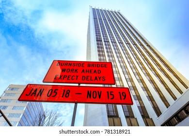 Portland, Oregon, United States - Dec 19, 2017: Road sign behind building of Wells Fargo Center in downtown Portland