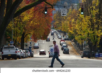 PORTLAND, OREGON, UNITED STATES - NOV 8, 2012: A man rushing through a crossing with colorful trees on both sides of the road. Editorial Use Only.
