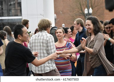 Portland, Oregon, USA 04.02.2017 : An Asian Man In A Black Shirt Dancing With A short Brunette Haired Woman In A Brown Sweater In The City With A Group Of People During Spring Outdoors