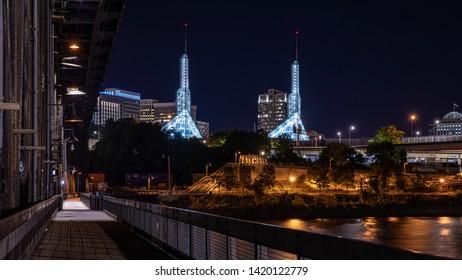 Portland, Oregon \ USA - 09 June 2019: Night photo of Oregon Convention Center from lower pedestrian walkway of Steel bridge over Willamette river.