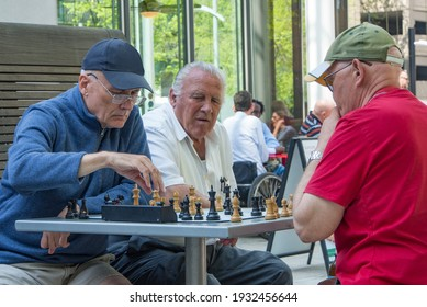 Portland, Oregon USA - April 20, 2015:  Three old retired men playing an intense game of chess at a park on an outdoor table with a timer