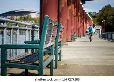PORTLAND, OREGON, USA - APRIL 7 2020: Benches and bicyclist wearing protective mask due to coronavirus along the Eastbank Esplanade along the Willamette River in Portland, Oregon.
