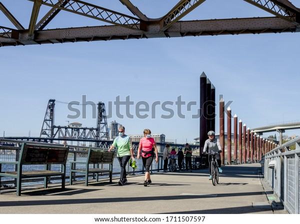 PORTLAND, OREGON, USA - APRIL 8 2020: Two women walking along the Eastbank Esplanade multi use path wearing protective masks due to the covid-19 pandemic.