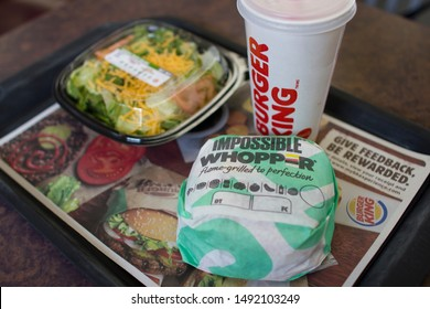 Portland, Oregon, USA - Aug 30, 2019: An Impossible Whopper sandwich and a side garden salad in a Burger King restaurant in Portland. The sandwich is made with an Impossible brand plant-based patty.