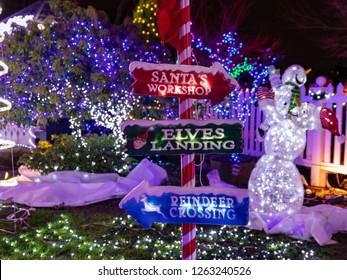 Portland, Oregon \ USA - December 15 2018: Signpost at Victorian Belle mansion during The Miracle of Million lights show shows direction to reindeer crossing, Santa's workshop and elves landing