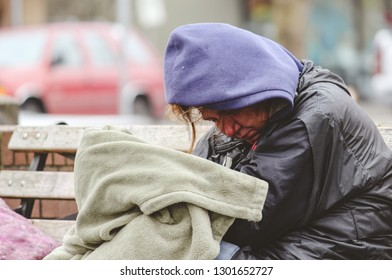 Portland, Oregon USA, February 1, 2019. A color image of a homeless woman braving the cold and rain on a park bench.