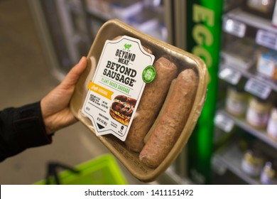 Portland, Oregon, USA - May 28, 2019: A customer chooses BEYOND MEAT brand Beyond Sausage at a Whole Foods Market grocery store. BEYOND MEAT is an American producer of plant-based meat substitutes.