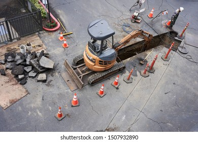 Portland, Oregon, USA - Sep 11, 2019: A worker is fixing underground drainage pipes in a parking lot.