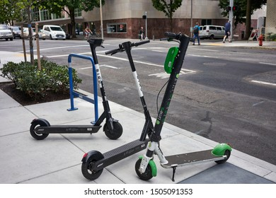 Portland, Oregon, USA - Sep 13, 2019: Bird branded and Lime branded dockless shared electric scooters are seen parked together by the roadside in downtown Portland.