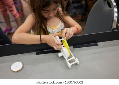 Portland, Oregon, USA - Sep 8, 2019: A girl tries to assemble a toy racing car with 3D printed parts at the Portland Mini Maker Faire held in Oregon Museum of Science and Industry (OMSI).