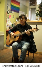 Portland, Oregon/United States – 12/25/2018: A woman playing guitar in the Street Roots office of downtown Portland for Christmas. Street Roots is a Street Paper by people experiencing homelessness.