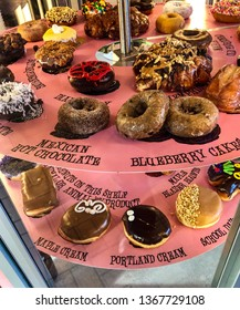 Portland, OR/USA - April 2019: A view of various doughnuts displayed for sale at Voodoo Donuts. Voodoo Donuts is a popular donut store located in Portland Oregon