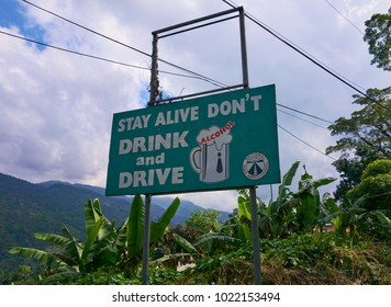 Portland Parish, Jamaica - January 1, 2014: Green Don't drink and drive road safety sign by the side of the B1 road in the Blue Mountains region of the Portland Parish, Jamaica.