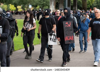 Portland, OR / USA - August 17 2019: Group of masked Antifa demonstrators wearing black clothes at the downtown protest. One carries banner that shows hammer and sickle with ACAB written on it.