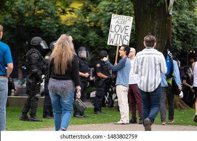 "Portland, OR / USA - August 17 2019: Protester at downtown Antifa demonstration holding sign in front of police that reads ""Spoiler alert: Love wins"""