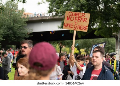 """Portland, OR / USA - August 17 2019: Protester holding a sign that reads """"Queer no fear, Hate not here"""" during Antifa downtown demonstration."""