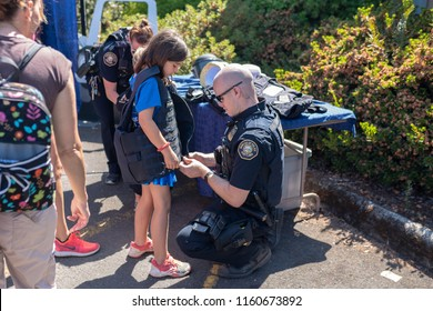 Portland, OR / USA - August 18 2018: Police officer putting Kevlar vest on a child at the event.