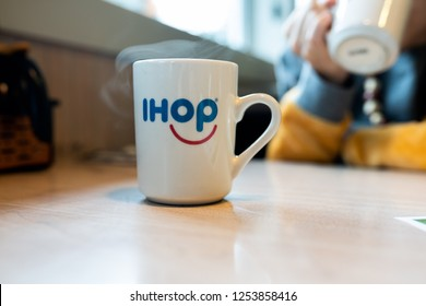 Portland, OR / USA - December 8 2018: Ihop cup with a hot coffee on a table with steam coming out of it.