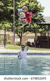 PORTLAND, USA - JULY 2 2017: Man is standing in the pool and holsing a stack of balloons
