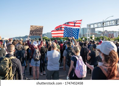 Portland, OR / USA - June 1 2020: Large crowd of protesters holding signs and upside down American flag on a Morrison bridge, during George Floyd killing demonstration.