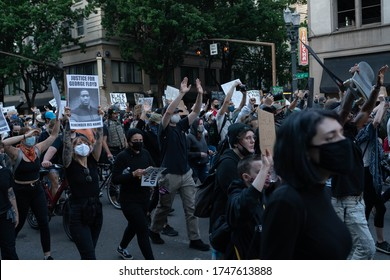 Portland, OR / USA - June 1 2020: Large crowd of protesters holding signs and banners at downtown demonstration against George Floyd killing.