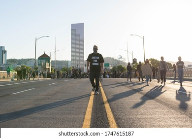"Portland, OR / USA - June 1 2020: Male protester wearing ""Justice for George"" black t-shirt in the middle of the Morrison Bridge during George Floyd killing demonstration."