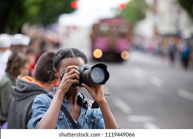 Portland, OR / USA - June 11 2016: Grand floral parade, African American female photographer taking pictures with canon dslr camera.