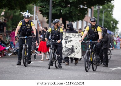 Portland, OR / USA - June 11 2016: Grand floral parade. Police officers on bicycles riding along side anti cop masked demonstrators.