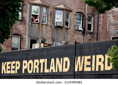 Portland, OR / USA - June 22 2018: Keep Portland weird sign with ancient building in the background