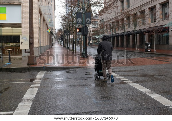Portland, OR / USA - March 29 2020: Man with a baby stroller crossing the empty downtown intersection in rain, during coronavirus pandemic city lock-down.