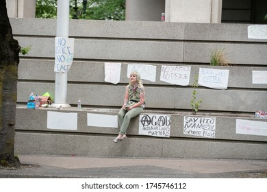 Portland, OR / USA - May 29 2020: Lone female demonstrator on the steps of Justice center surrounded by signs and banners taped to the wall.
