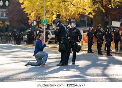 Portland, OR / USA - November 17 2018: Demonstrator in downtown Portland on his knees in the middle of a street. Two police officers attempt to reason with an adult male.