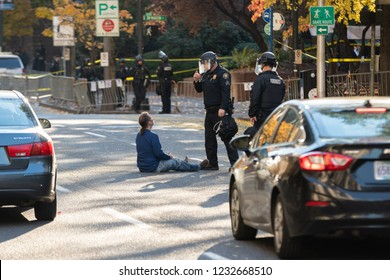 Portland, OR / USA - November 17 2018: Adult male protester blocking traffic by sitting in the middle of a street. Two uniformed police officers try to reason with the demonstrator.