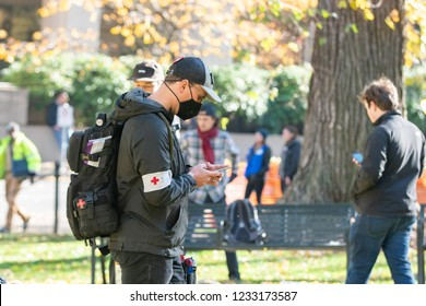 Portland, OR / USA - November 17 2018: Masked demonstrator with a medical red cross on the arm band (street medic) and asexual pride flag on backpack, during downtown Antifa protest.