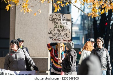 "Portland, OR / USA - November 17 2018: Female demonstrator with a sign reading ""Sexist, Woman-hating pro-rape scum: go home, we won't be intimidated"" at patriot prayer counter protest."