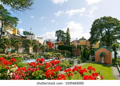 Portmeirion, UK: September 01, 2019: The gardens at the centre of Portmeirion village with flowers, ornate pond and Italian style hotel accomodation built into the cliff side.